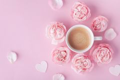 Morning coffee and beautiful rose flowers on pink pastel table top view. Cozy breakfast for Womens or Valentines day. Flat lay stock photo
