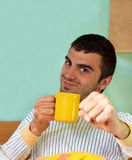 Morning coffee in bed. Young handsome man wearing pyjamas is in a very good mood and drinking morning coffee Royalty Free Stock Photography