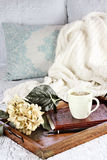 Morning Coffee in Bed. A hot relaxing cup of coffee with a book and flowers in a serving tray sitting on a comfortable bed with blanket. Extreme shallow depth of stock images