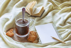 Morning coffee with biscuits, book,  paper notepad, pencil on ye Royalty Free Stock Photo