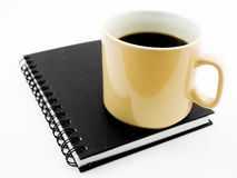 Morning coffee on black notebook. Isolated on white royalty free stock image