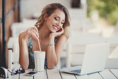 Morning coffee a business woman in a summer cafe. Happy woman,a brunette with long curly hair and brown eyes,a beautiful smile,sitting at a white table in a Royalty Free Stock Photography