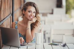 Morning coffee a business woman in a summer cafe. Happy woman,a brunette with long curly hair and brown eyes,a beautiful smile,sitting at a white table in a Royalty Free Stock Image