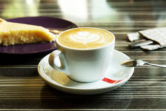Morning coffee with cheesecake. Morning cappuccino coffee and cheesecake. Cheesecake and kitchen appliances on the background. Coffee with art foam Royalty Free Stock Images