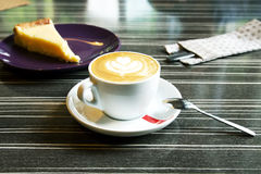 Morning coffee with cheesecake. Morning cappuccino coffee and cheesecake. Cheesecake and kitchen appliances on the background. Coffee with art foam Royalty Free Stock Image