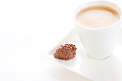 A morning coffee and chocolate. A cup of creamy black coffee on a square saucer with a chocolate, focussed on the chocolate Stock Photos