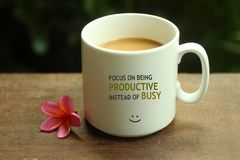 Morning Coffee concept. Work inspirational quote on a mug - Focus on being productive instead of busy. With white mug of coffee