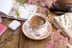Morning coffee in a cozy cafe. Planning the day in notepad. Decor of pink flowers. Free space for text. Card. Copy space.  stock photography