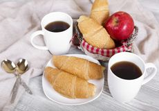 Morning coffee and croissants. Coffee mugs, fragrant croissants, apple and croissants in a basket Stock Images
