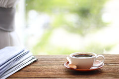 Morning coffee, Cup of coffee with newspapers, near the window.b Royalty Free Stock Images