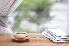 Morning coffee, Cup of coffee with newspapers, near the window.b Royalty Free Stock Image