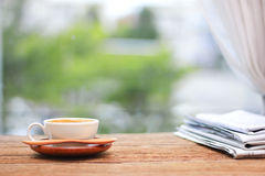 Morning coffee, Cup of coffee with newspapers, near the window.b Stock Photo