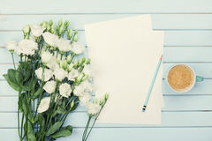 Morning coffee cup, empty paper list, pencil, and bouquet of white flowers eustoma on blue rustic table from above. Woman desk. Royalty Free Stock Photo
