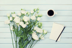 Morning coffee cup, empty paper list, pencil, and bouquet of white flowers eustoma on blue rustic table top view. Flat lay. Stock Image