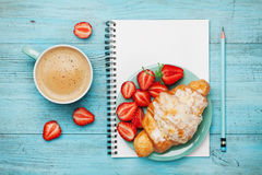 Morning coffee cup with fresh croissant, strawberry and empty notebook on turquoise rustic table from above, tasty breakfast Royalty Free Stock Photography
