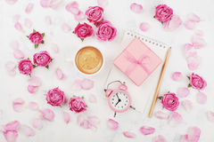 Morning coffee cup, gift box, alarm clock and pink rose flowers on white table top view in flat lay style. Greeting card. Stock Photo