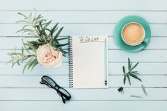 Morning coffee cup, notebook with to do list, pencil, eyeglasses and vintage rose flower in vase on blue rustic table from above. Stock Photos