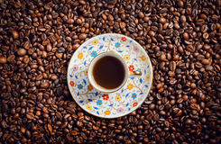 Morning coffee cup with saucer on background with beans, top view. Royalty Free Stock Photography