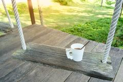 Morning coffee cup on wood swing in green garden space Stock Photos