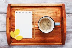 Morning coffee and empty notebook on wooden tray top view. Cozy autumn breakfast. Fall bucket list. Flat lay. Morning coffee and empty notebook on wooden tray Royalty Free Stock Photos