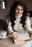 Morning coffee,enjoyment,she closed her eyes. Amazing girl reading a book and smiling. She reads with interest. the Stock Photo
