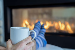Morning coffee by the fireplace. Mans hand holding a white coffee cup with his feet up by a fireplace wearing blue and white striped socks royalty free stock images