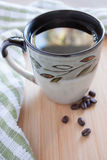 Morning Coffee. A fresh cup of coffee sits on the counter with a few beans beside it Royalty Free Stock Images