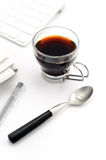Morning coffee in glass cup. Coffee in glass cup with teaspoon, pen, newspaper and keyboard de-focused royalty free stock photography