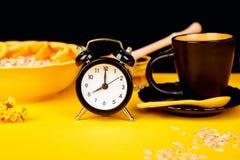 Morning coffee, granola breakfast, alarm clock. Morning coffee, granola breakfast with fruit near black alarm clock, vase flower on yellow background Stock Images