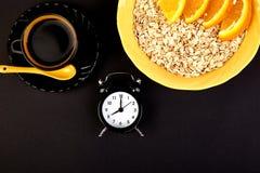 Morning coffee, granola breakfast, alarm clock. Morning coffee, granola breakfast with fruit near alarm clock, black background. Flat lay. Copy space. Top view Stock Photos