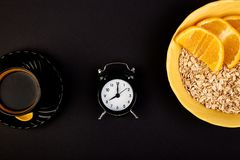 Morning coffee, granola breakfast, alarm clock. Morning coffee, granola breakfast with fruit near alarm clock, black background. Flat lay. Copy space. Top view Stock Photography