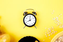 Morning coffee, granola breakfast, alarm clock. Morning coffee, granola breakfast with fruit near black alarm clock, vase flower on yellow background. Flat lay Royalty Free Stock Photography
