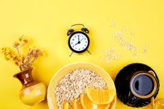 Morning coffee, granola breakfast, alarm clock. Morning coffee, granola breakfast with fruit near black alarm clock, vase flower on yellow background. Flat lay Stock Photos