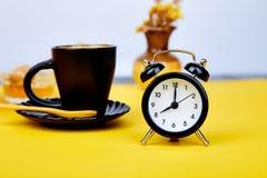 Morning coffee, granola breakfast, alarm clock. Morning coffee, granola breakfast with fruit near black alarm clock, vase flower on yellow background. Flat lay Royalty Free Stock Photo