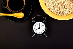 Morning coffee, granola breakfast, alarm clock. Morning coffee, granola breakfast with fruit near alarm clock, black background. Flat lay. Copy space. Top view Royalty Free Stock Photography