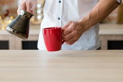 Morning coffee habit urban lifestyle man cup. Morning coffee habit. Urban lifestyle. Man hands with jezve and red cup. Copy space stock photography