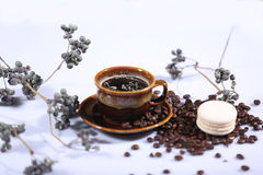 Morning coffee. Hot coffee in a brown cup, coffee beans and branches around royalty free stock images
