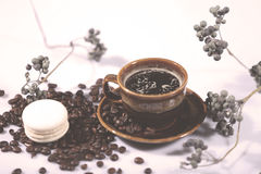 Morning coffee. Hot coffee in a brown cup, coffee beans and branches around royalty free stock photos