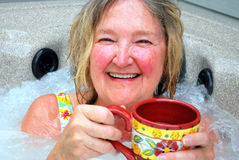 Morning coffee and the hot tub. Mature female beauty enjoying her morning coffee and the hot tub stock photos