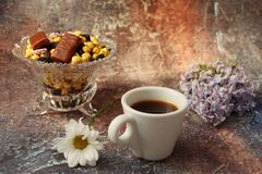 Morning coffee in a hurry: a cup of coffee, flowers in a vase, dried fruits and sweets in a vase, a burning candle stock photo