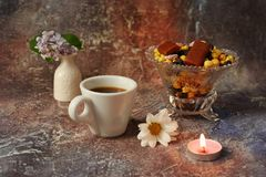 Morning coffee in a hurry: a cup of coffee, flowers in a vase, dried fruits and sweets in a vase, a burning candle royalty free stock photos