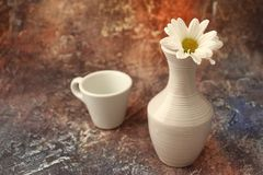 Morning coffee in a hurry: a cup of coffee, flowers in a vase, dried fruits and sweets in a vase, a burning candle stock image