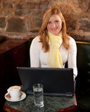 Morning coffee in internet cafe. Beautiful young girl checking news on web and drinking coffe Stock Images