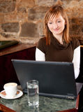 Morning coffee in internet cafe. Beautiful young girl checking news on web and drinking coffe Royalty Free Stock Photo