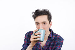 Morning coffee. Isolated portrait of a man wearing pajamas and drinking his morning coffee, looking into the camera Stock Image