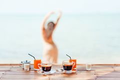 Morning coffee and juice with woman silhouette on the beach back. Close up of coffee cups and a cheerful girl on background Stock Image