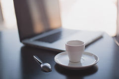 Morning coffee and laptop. Morning in a cafe,  open laptop lay at on the table, Cup of coffee in focus Stock Photography