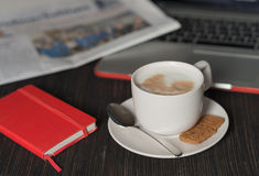 Morning coffee with milk foam , newspaper, laptop and notebook Royalty Free Stock Image