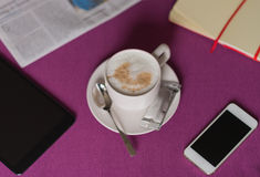 Morning coffee with milk foam , newspaper, tablet and smartphone Royalty Free Stock Images