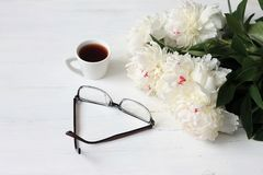 Morning coffee mug, glasses and white peonies flowers on white wooden table, breakfast stock photos